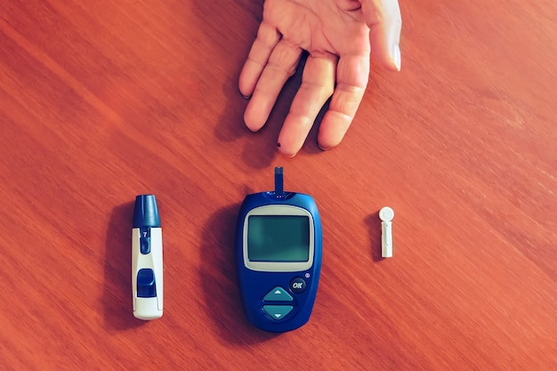 Le mani di una signora che misurano la glicemia, il glucosio con un test casalingo per controllare il suo diabete. il glucometro e gli aghi per il test giacciono su un tavolo di legno. goccia di sangue sul dito da vicino