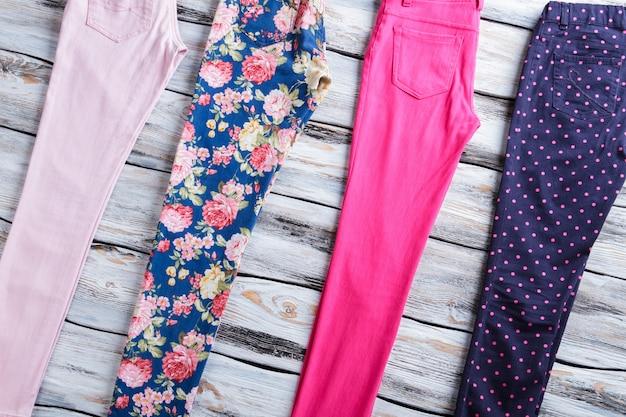 Pantaloni da donna di diverso colore. pantaloni rosa acceso e floreali. vetrina con vestiti nuovi. merce dal miglior fornitore.