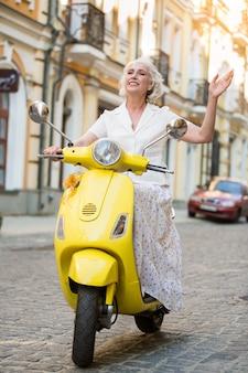 Signora sulla mano delle onde del motorino.