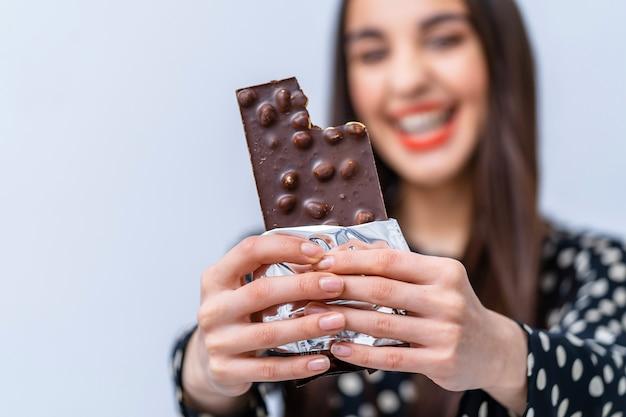 Signora che mostra la barretta di cioccolato con i dadi alla telecamera. dolce concetto di vita.
