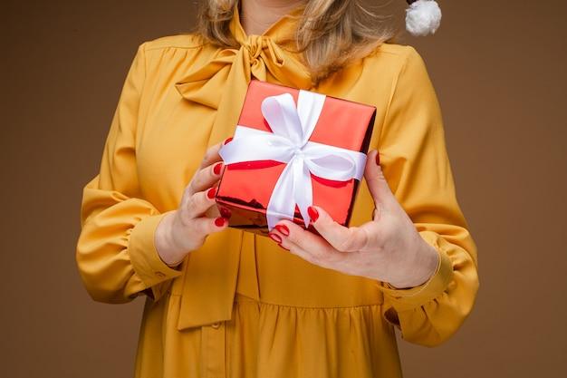 Signora che mostra un pacco quadrato con un regalo, coperto con un pacco di carta rosso e legato con un nastro bianco. anno nuovo concetto