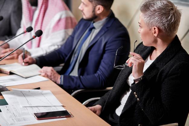 Signora in vestito che ascolta il leader politico che ha discussione, seduto alla scrivania in sala riunioni, coworking. incontro senza legami, concetto di affari