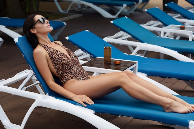 Signora che si abbronza su sedie a sdraio blu, posa in costume da bagno alla moda con stampa leopardata, occhiali scuri, con bevande