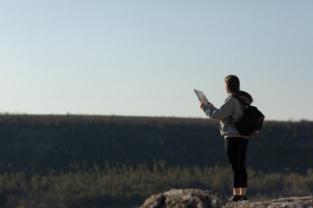 Signora viaggiatrice con zaino in piedi sulla montagna rocciosa ed esplora il percorso di una mappa cartacea