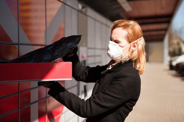 La signora che indossa una maschera facciale riceve un pacco o un pacco da una donna post terminal in maschera respiratoria