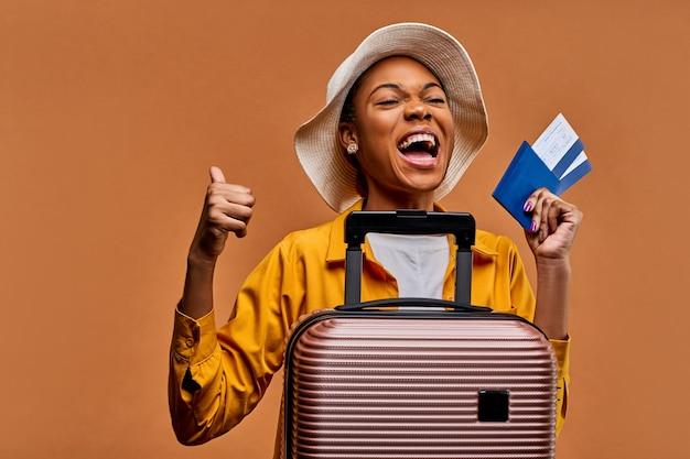 Signora con un cappello bianco in una giacca gialla con una valigia con un passaporto blu e due biglietti gioie e mostra un simbolo del simile - grande dito in su. concetto di viaggio