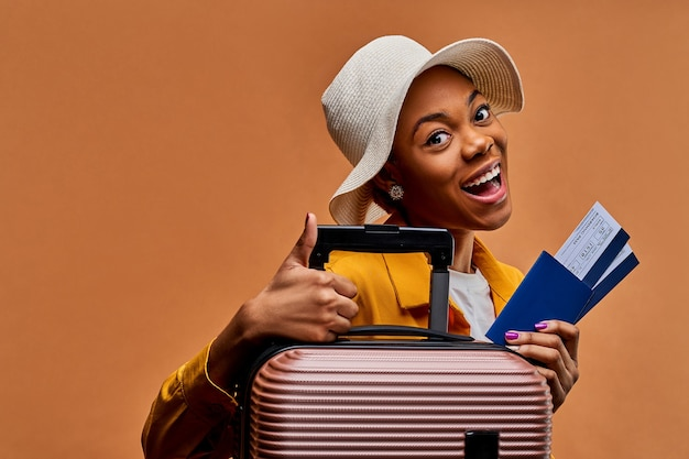 La signora con un cappello bianco in una giacca gialla con una valigia con un passaporto blu e due biglietti mostra un simbolo di simile - grande dito in su. concetto di viaggio