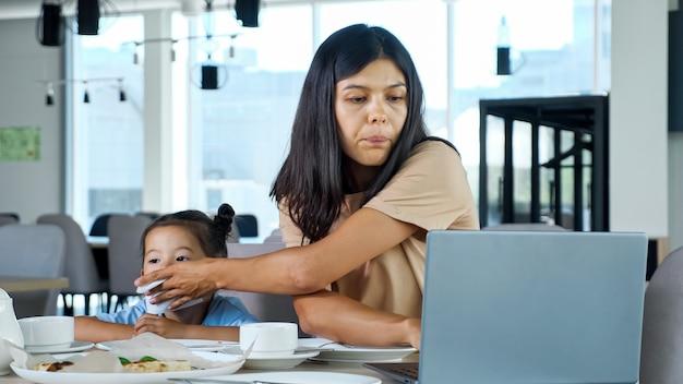 La signora pulisce la bocca della figlia. la mamma asiatica concentrata della donna d'affari pulisce il bambino seduto al tavolo con il tè e il computer portatile grigio vista ravvicinata