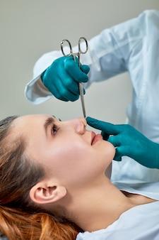 Signora con cerotto sul naso, dottore che esamina il viso dei pazienti dopo la chirurgia plastica