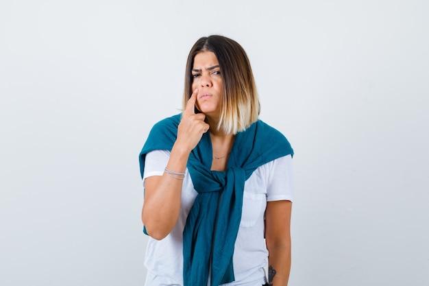 Signora con un maglione legato che punta alla palpebra in maglietta bianca e sembra triste, vista frontale.