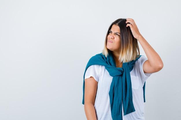 Signora con maglione legato in t-shirt bianca che guarda lontano mentre si gratta la testa e sembra smemorata, vista frontale.