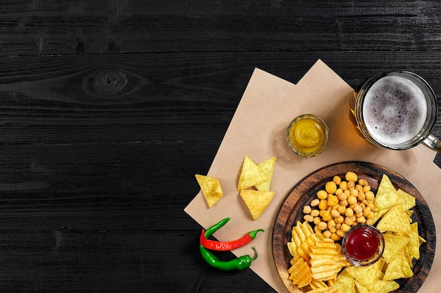 Birra chiara e spuntini sulla vista dall'alto di patatine da tavola in legno nero con copyspace