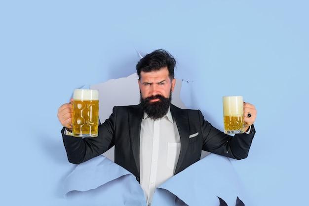 Lager e birra scura uomo barbuto tiene birra artigianale guardando attraverso il buco della carta beve alcol per il tempo libero