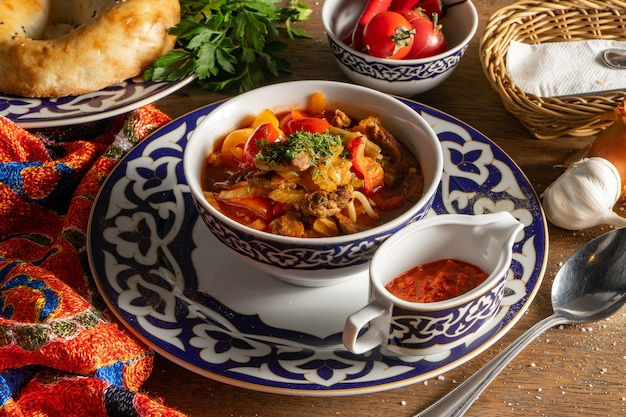 Lagman. il piatto nazionale uzbeko è una zuppa profumata con noodles e pezzi di agnello, fritti con verdure ed erbe aromatiche. servito con una salsa piccante adjika.