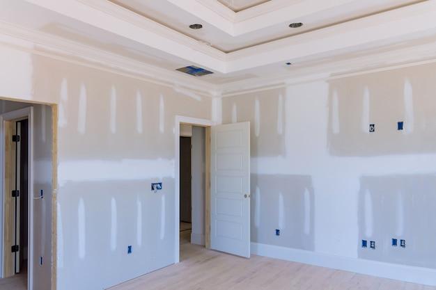 Posa intonaco di gesso sulle pareti e sul soffitto di una casa di nuova costruzione alle cuciture del muro a secco