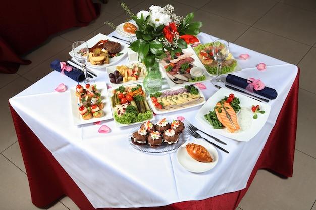 Tavola apparecchiata con una varietà di piatti, pesce, pasticcini, sottaceti
