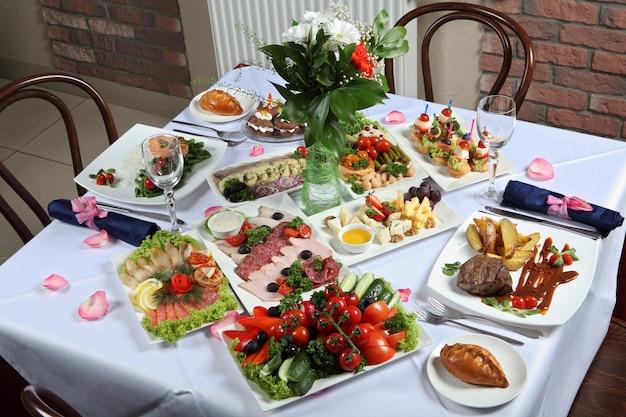 Tavola apparecchiata con una varietà di piatti, servita con una tovaglia bianca e un bouquet di fiori.