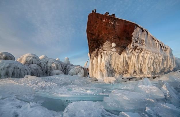 Il lago baikal è coperto di ghiaccio e neve, freddo intenso, ghiaccio azzurro e denso. ghiaccioli pendono dalle rocce. il lago baikal è una gelida giornata invernale. posto incredibile, patrimonio, bellezza della russia?