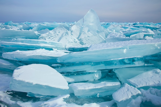 Lago baikal in inverno. bella vista di acqua ghiacciata. blocchi testurizzati di ghiaccio blu chiaro. montagne e paesaggi dalla trama ghiacciata