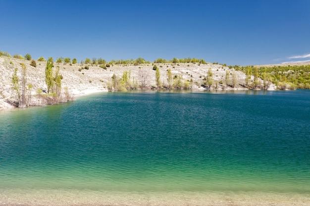 Lago blu acqua turchese, alberi su una sponda ripida, giornata limpida.