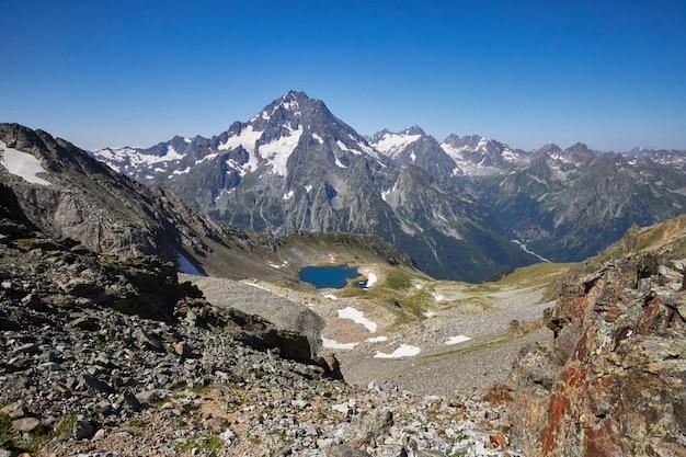 Lago montagne del caucaso in estate, lo scioglimento della cresta del ghiacciaio lago arkhyz sofia. belle alte montagne della russia, limpida acqua ghiacciata. estate in montagna, escursione. favoloso paesaggio e cielo blu