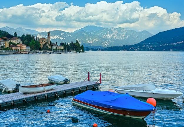 Vista di estate del puntello del lago como (italia) con le barche nella parte anteriore.
