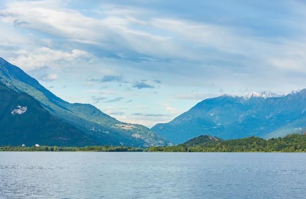 Vista nuvolosa di estate del lago como (italia) con neve sulla cima del supporto.