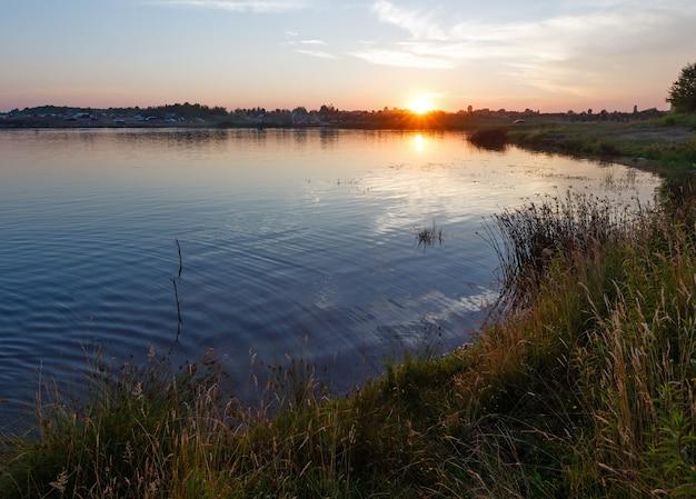 Vista del tramonto estivo sul lago con riflesso del sole e auto sulla riva. tutte le persone sono irriconoscibili.
