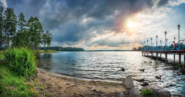 Lago valdai sotto i raggi del sole e il molo vicino al monastero iversky