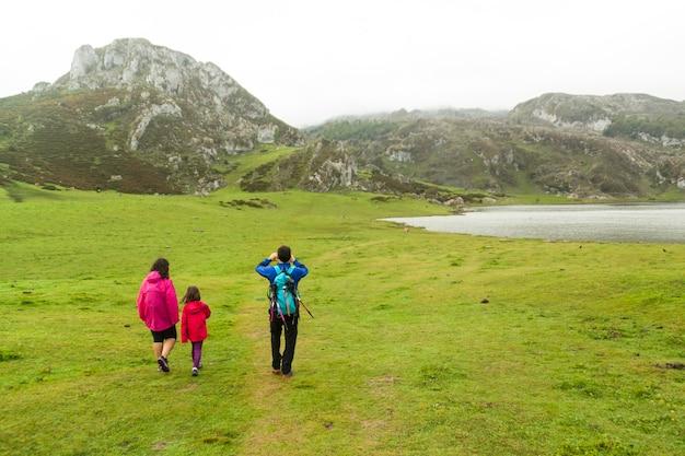 Laghi di covadonga con nebbia in primavera. turisti che fanno un'escursione sul lago enol. asturie, spagna