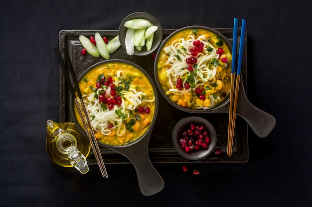 Laksa con zucca e latte di cocco, spaghetti di riso, broccoli e semi di melograno