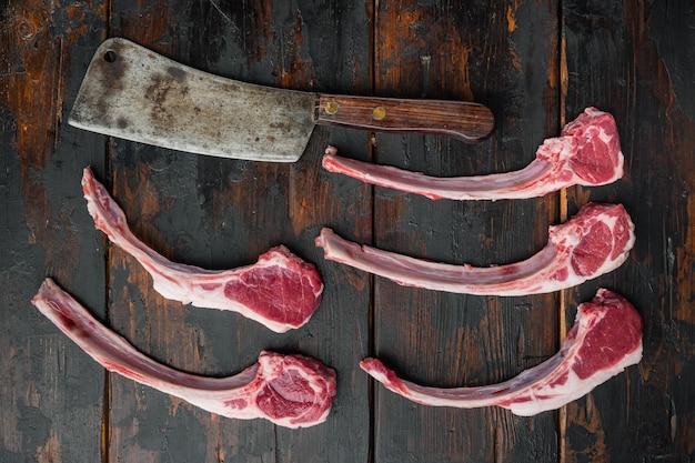Costolette di agnello set rifinito alla francese e vecchio coltello da macellaio, su vecchio tavolo di legno scuro, vista dall'alto piatta