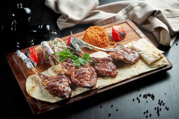 Carré di agnello cotto alla griglia con pane pita, bulgur e verdure grigliate su una tavola di legno. shashlik turco. primo piano, messa a fuoco selettiva
