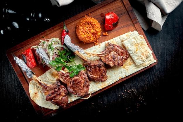 Carré di agnello cotto alla griglia con pane pita, bulgur e verdure grigliate su tavola di legno. shashlik turco.