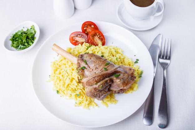 Stinco di agnello (stinco) con riso, prezzemolo, pomodori e salsa su un piatto bianco. piatto tradizionale. primo piano, messa a fuoco selettiva.
