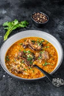Zuppa di agnello kharcho con carne di montone, riso, pomodori e spezie in una ciotola