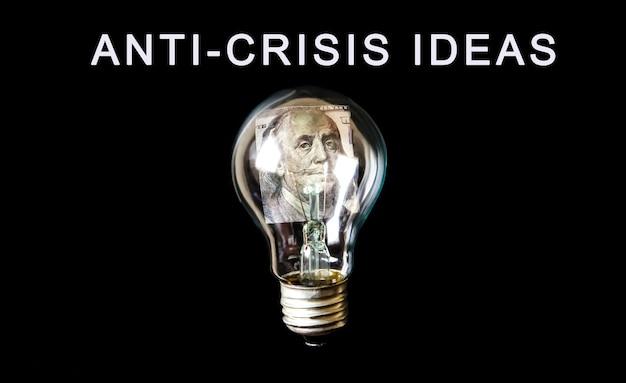 Lampadina con dentro i soldi. strategia anti-crisi. in aumento sul prezzo. nuovo concetto di idea. senza soldi. crisi economica, povertà, concetto di disoccupazione. isolamento per il coronavirus. tassi di inflazione.