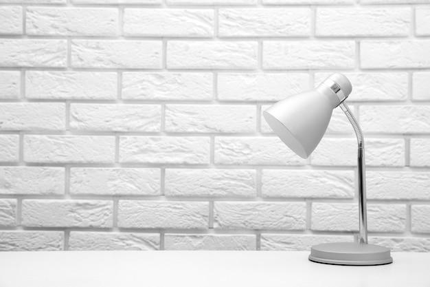 Lampada sulla scrivania sulla superficie del muro di mattoni