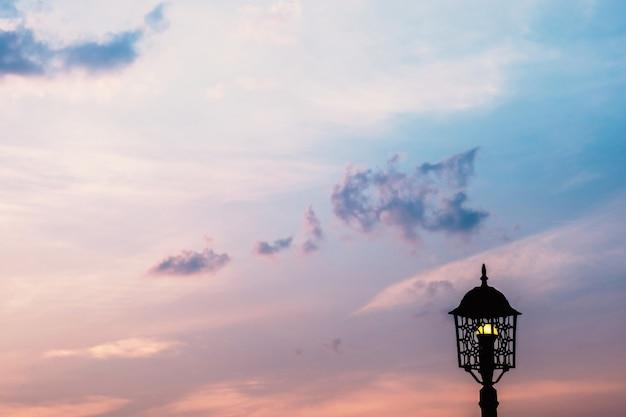 Lampada e cielo luminoso dorato durante la vista del tramonto serale.