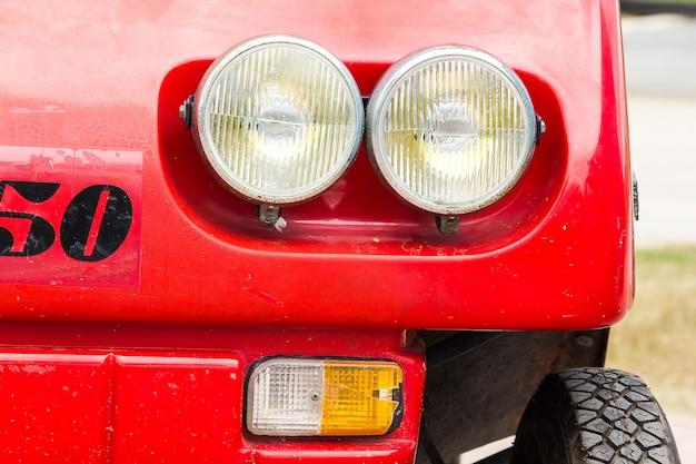 Parti della lampada davanti all'automobile rossa dell'annata