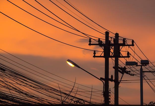 Lampione e linea telefonica con un tramonto sullo sfondo della strada