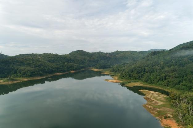 Colpo di drone di vista aerea del paesaggio della montagna intorno alla foresta pluviale tropicale della diga in tailandia