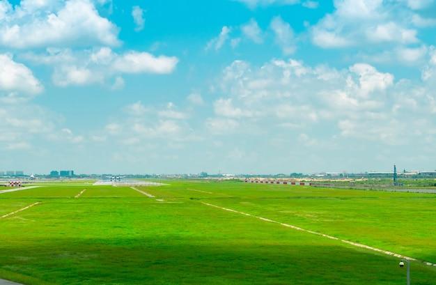 Paesaggio della pista dell'aeroporto e del campo di erba verde con cielo blu e nuvole bianche taxiway