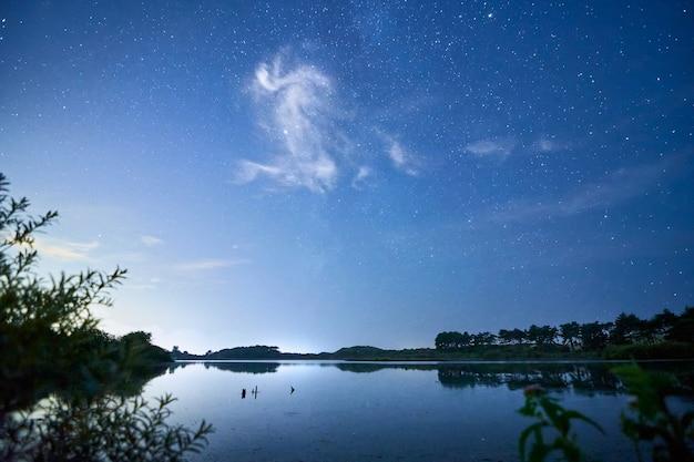 Paesaggio di un bellissimo lago di notte con nuvole e stelle