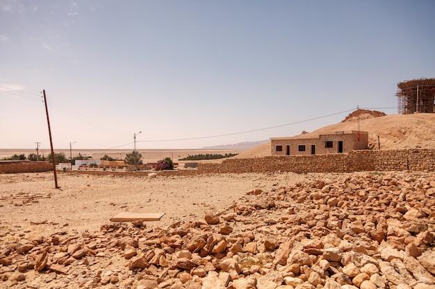 Paesaggio dell'oasi di chebika nel deserto del sahara. rovine insediamento e palma. oasi di montagna con vista panoramica in nord africa. situato a piedi jebel el negueba. montagne dell'atlante nel pomeriggio soleggiato. tozeur, tunisia