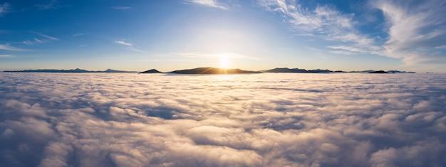 Paesaggio sopra le nuvole con picchi di montagna all'alba. cloudscape drammatico dalla vista aerea.