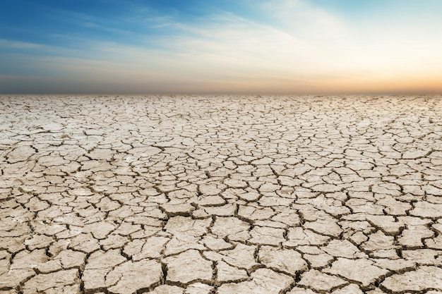 Abbellisca il terreno incrinato, terreno del deserto della terra con il cielo