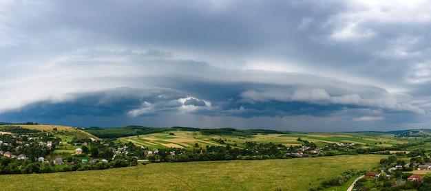 Paesaggio di nuvole scure che si formano sul cielo tempestoso durante il temporale sopra l'area rurale.