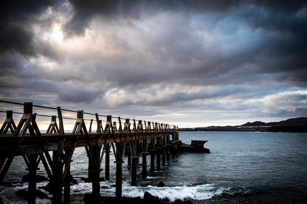 Paesaggio di un molo di legno sul mare in un luogo roccioso e bellissimo - nessuno sul posto e maltempo - lanzarote, isole canarie