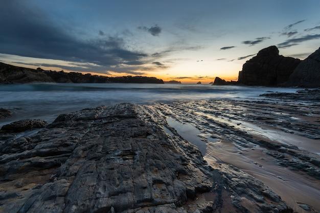 Paesaggio al tramonto nella spiaggia di portio. liencres. cantabria. spagna.
